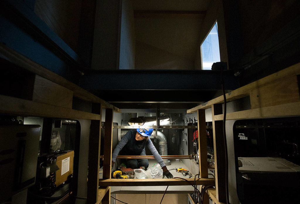 In the space between the ceiling and floor, Liliana Beltran crawls through tight spots while wiring a pilothouse at Nichols Brothers Boat Builders. (Andy Bronson / The Herald)