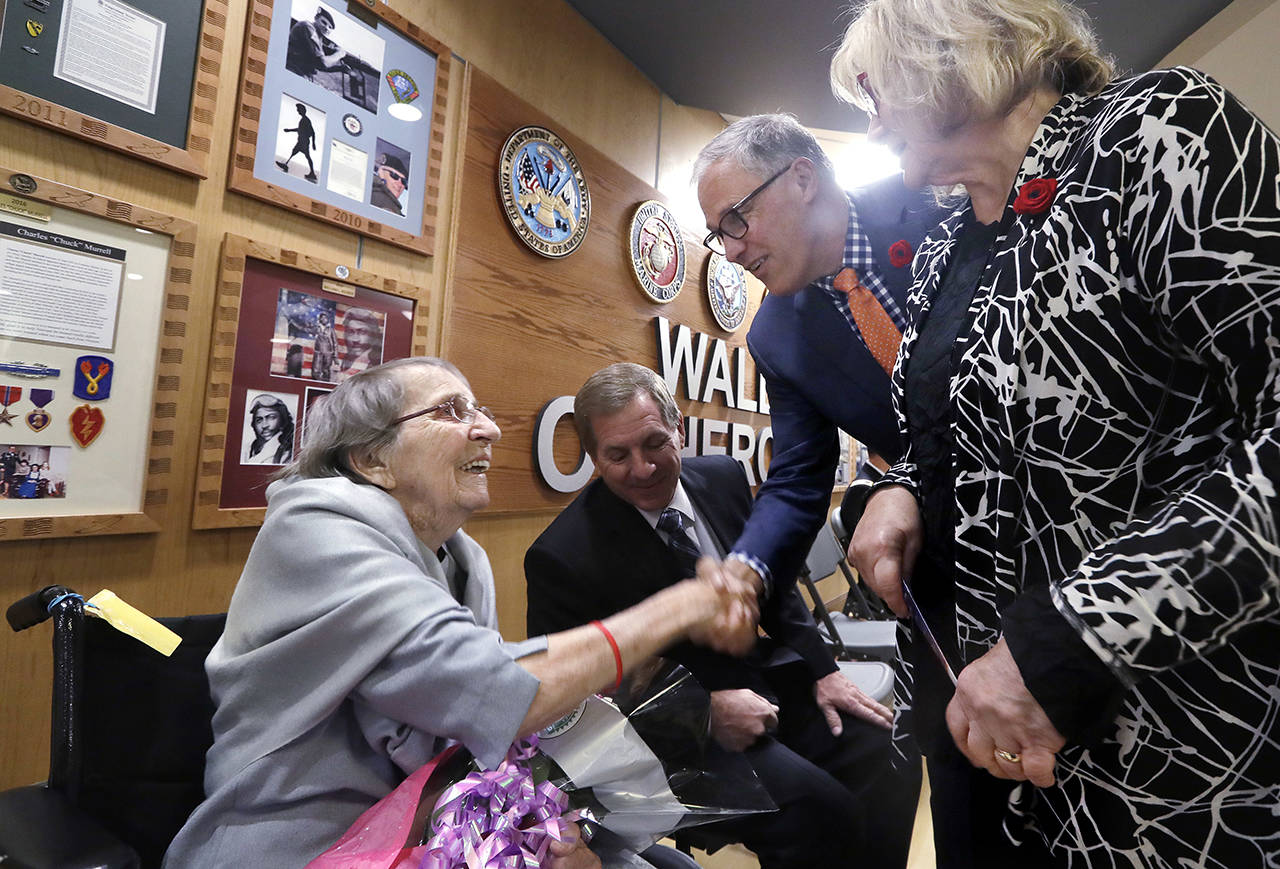 U.S. Army Nurse Corps veteran Frances E. Harman, 98 (left), who served as a first lieutenant in World War II, smiles as she is greeted by Gov. Jay Inslee and his wife, Trudi Inslee, before a ceremony honoring her service on Nov. 8 in Seattle. Harman's son, David Harman, is seated beside her. (AP Photo/Elaine Thompson, file)