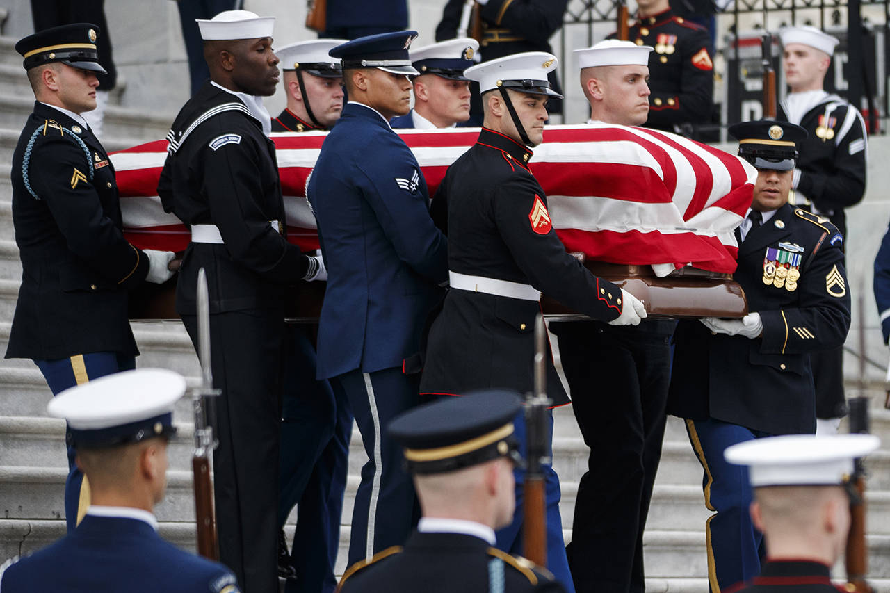 The flag-draped casket of former President George H.W. Bush is carried by a joint services military honor guard from the U.S. Capitol on Wednesday in Washington. (Shawn Thew/Pool Photo via AP)