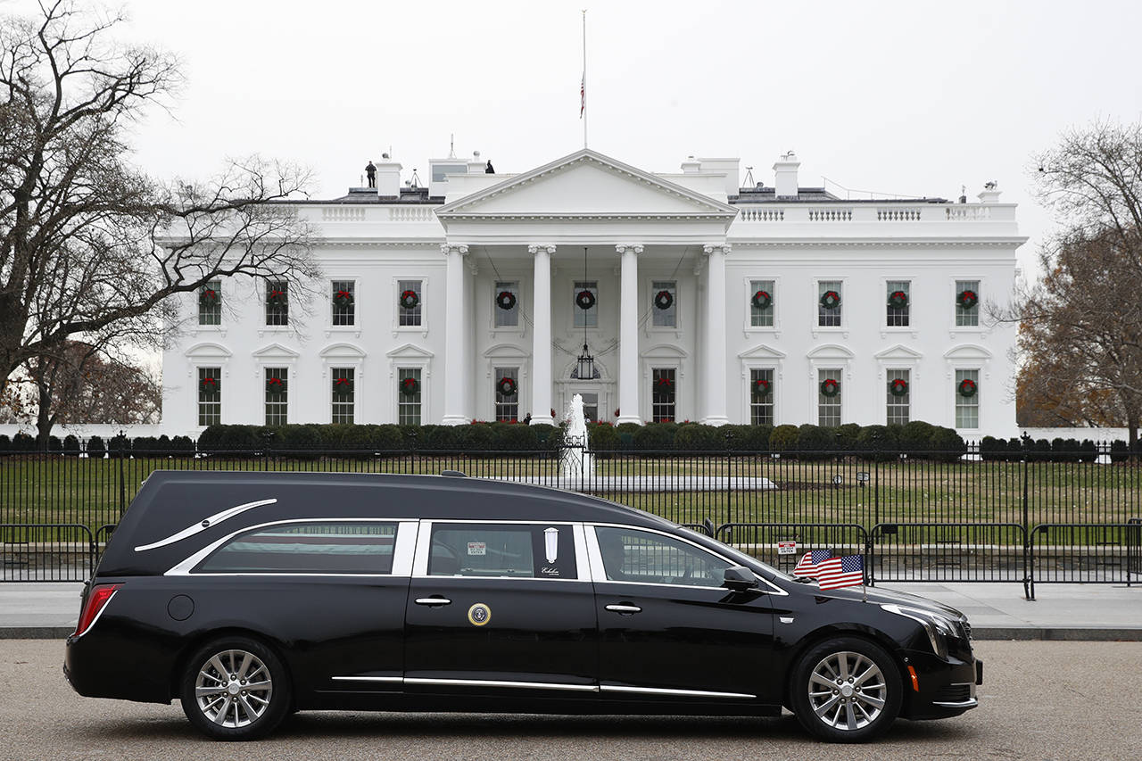 The hearse carrying the flag-draped casket of former President George H.W. Bush passes by the White House from the Capitol, heading to a State Funeral at the National Cathedral on Wednesday in Washington. AP Photo/Jacquelyn Martin)