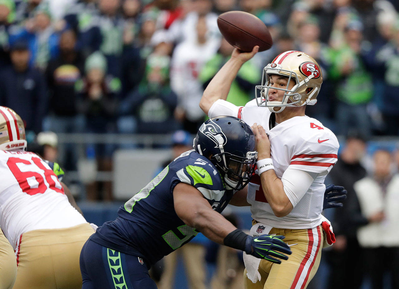 49ers quarterback Nick Mullens passes under pressure from Seahawks middle linebacker Bobby Wagner during the first half of a game on Dec. 2, 2018, in Seattle. (AP Photo/Elaine Thompson)