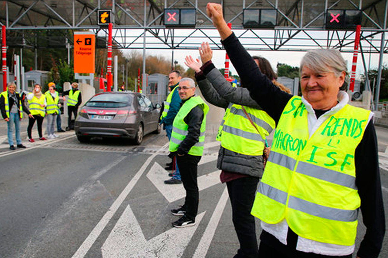 """A demonstrator wearing a yellow jacket reading """"Macron give us the wealth tax"""" protests at the toll gates on a motorway Wednesday at Biarritz southwestern France.The concessions made by French president Emmanuel Macron's government in a bid to stop the huge and violent anti-government demonstrations seemed on Wednesday to have failed to convince protesters, with trade unions and disgruntled farmers now threatening to join the fray. (AP Photo/Bob Edme)"""