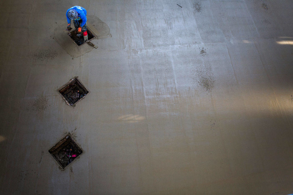 A Tiger Construction worker smooths out concrete at the construction site of Tambark Creek Elementary School on Friday in Bothell. (Olivia Vanni / The Herald)