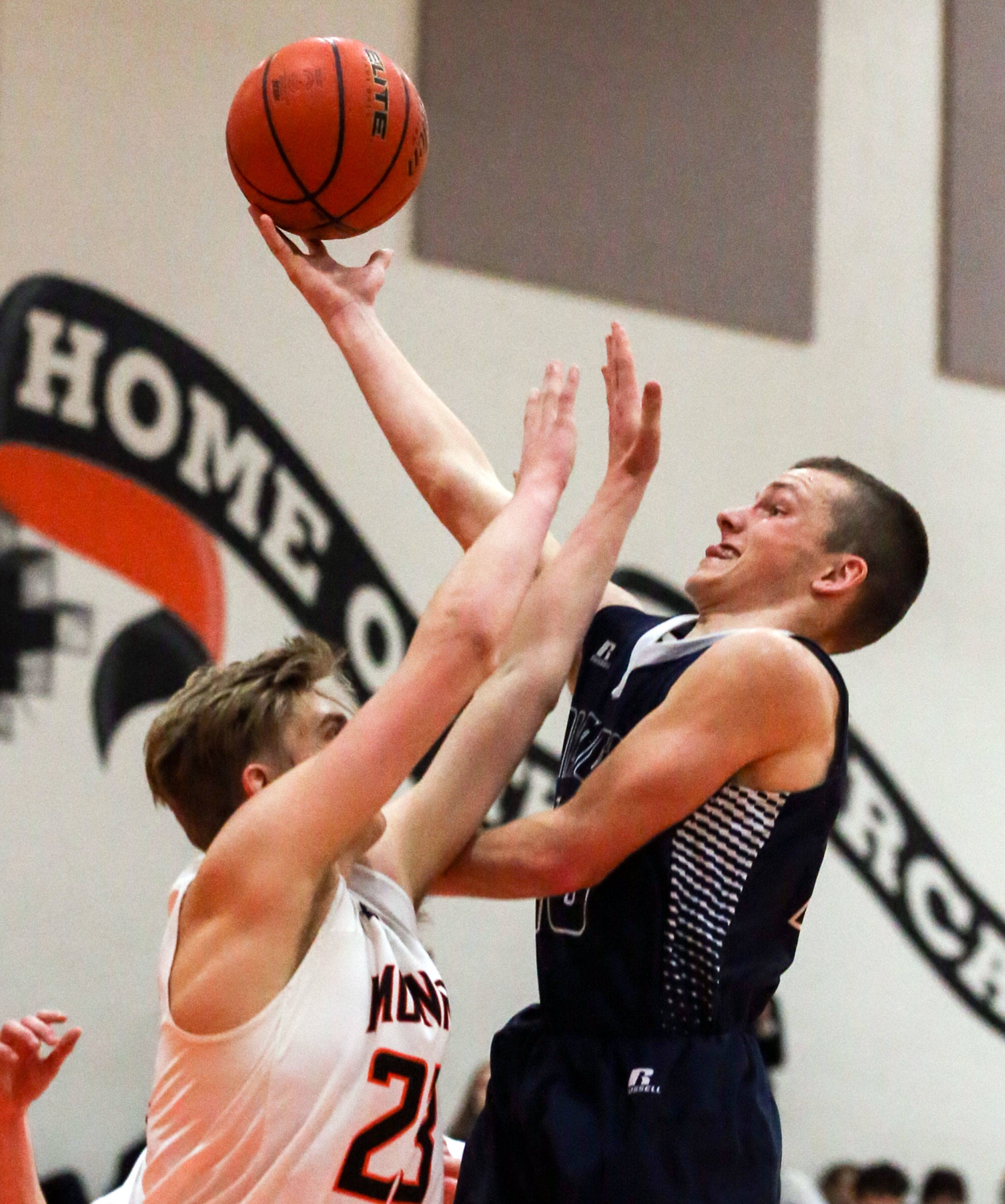 Arlington's Anthony Whitis (left) and attempts a shot over Monroe's Sam Olson on Friday night. Arlington won 62-54. (Kevin Clark / The Herald)