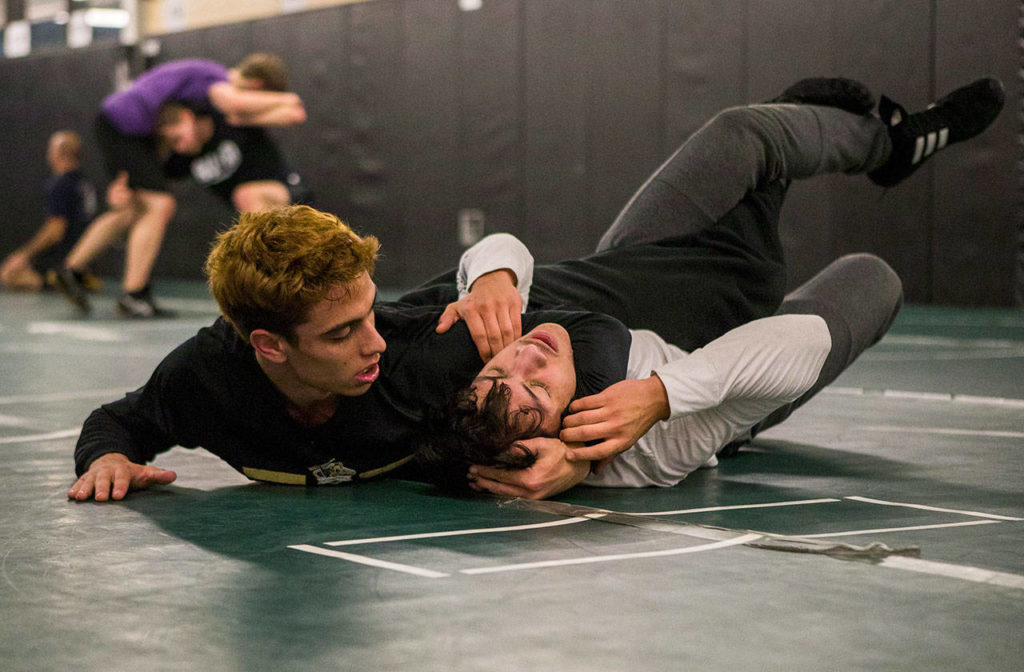 Marysville Getchell's Trey Padgett puts training partner Jesus Cabadas in a headlock during a team practice Dec. 11 in Marysville. (Olivia Vanni / The Herald)