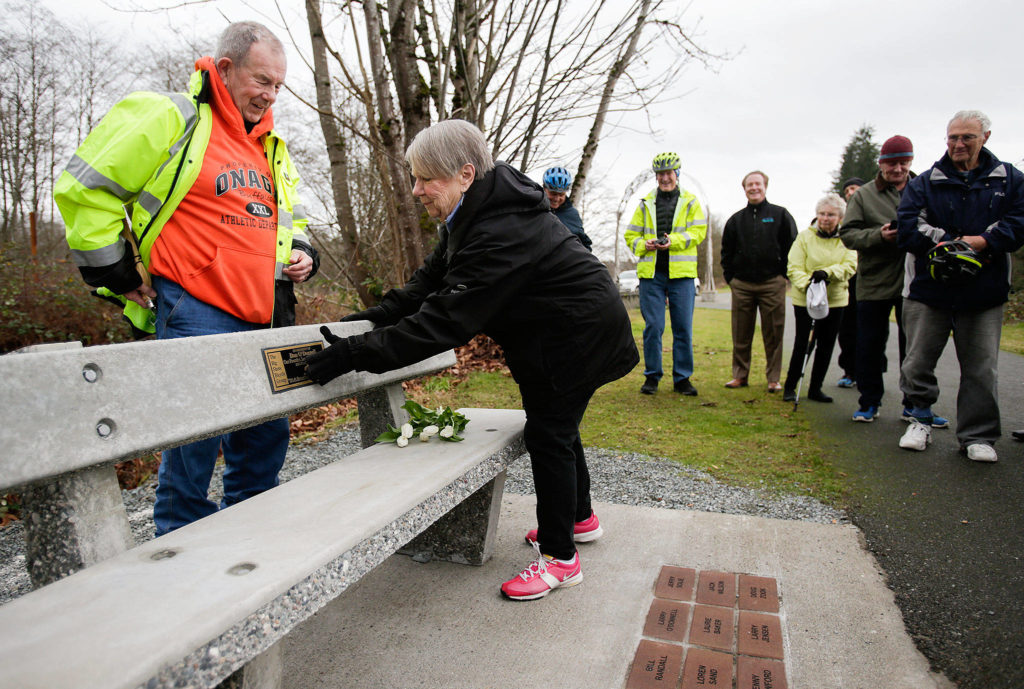 """After laying down flowers Wednesday, Dec. 19, Ann O'Donnell touches a plaque with her late husband Dan's name on it as family members and riders from """"The Big Shots Bicycle Group"""" pay their respects at a bench in founder Dan O'Donnell's name along the Centennial Trail in Arlington. (Andy Bronson / The Herald)"""
