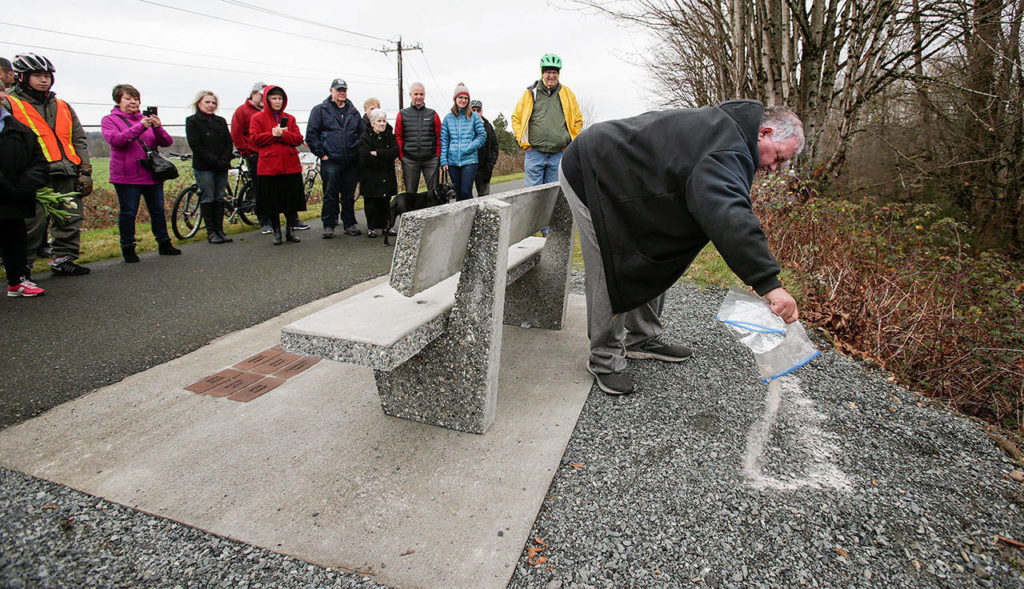 """Friends, family and members of the """"The Big Shots Bicycle Group"""" watch Jeff O'Donnell spread his father's ashes behind a bench in Dan O'Donnell's name along the Centennial Trail on Wednesday, Dec. 19, in Arlington. (Andy Bronson / The Herald)"""