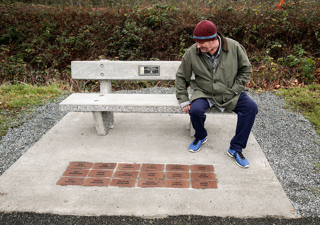 "Steve O'Donnell looks over a concrete bench in honor of his father Dan along the Centennial Trail on Wednesday, Dec. 19, in Arlington. Dan was the founder of ""The Big Shots Bicycle Group,"" whose member's names are inscribed in bricks at the base of the bench. (Andy Bronson / The Herald)"