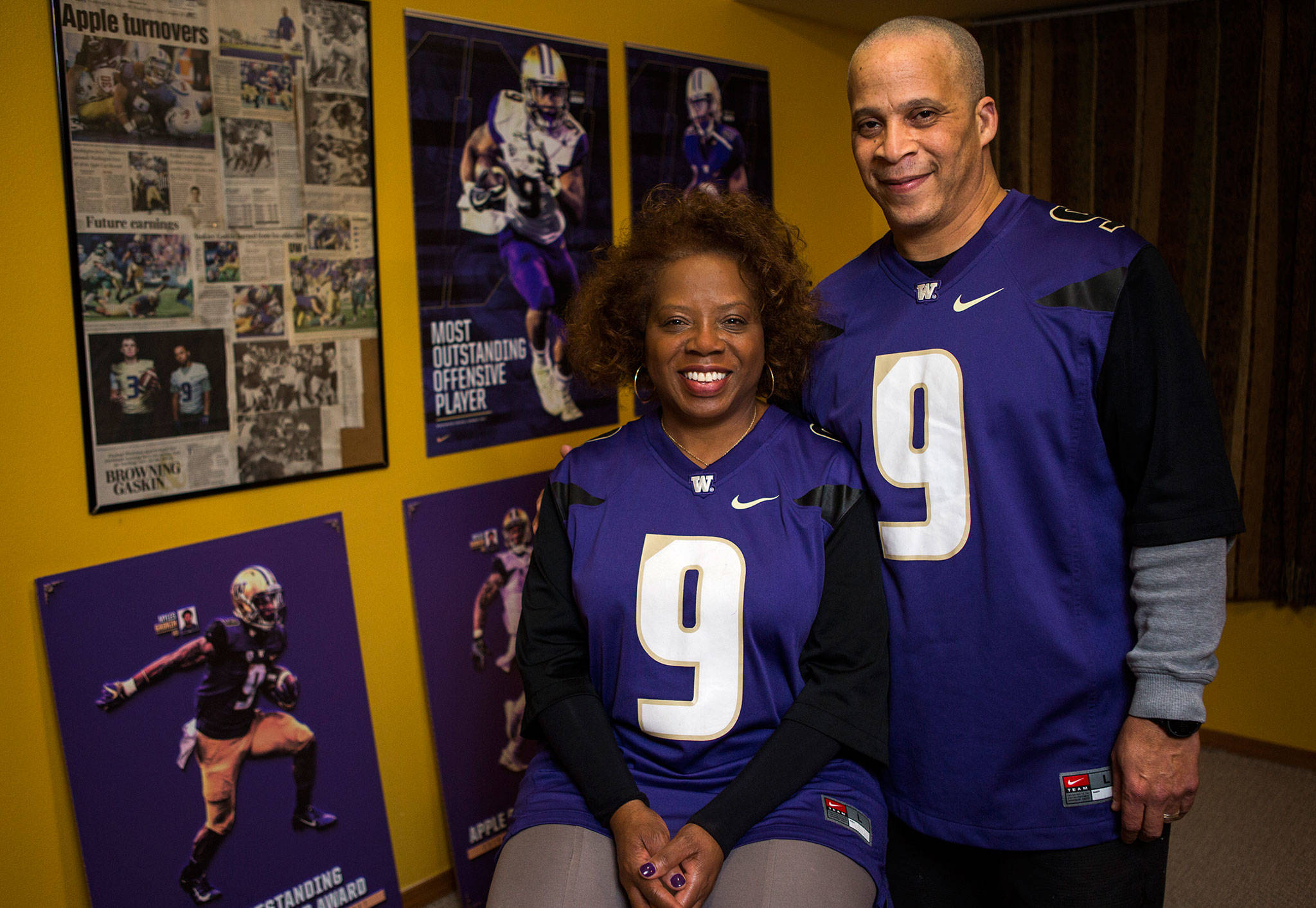 Robbie and Scott Gaskin, parents of University of Washington Husky football running back Myles Gaskin, stand near some memorabilia of his record-setting career at their home in Lynnwood. The family is in Pasadena this week to watch him play in the Rose Bowl. (Olivia Vanni / The Herald)