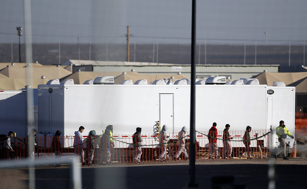 Migrant teens walk in a line through the Tornillo detention camp in Tornillo, Texas, on Thursday, Dec. 13. (AP Photo/Andres Leighton)