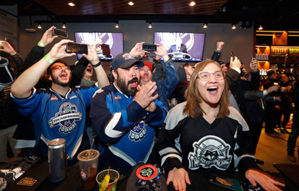 In this Dec. 4, 2018 photo, Ryan Kelly (left) Otto Rogers and Rebecca Moloney cheer the announcement of a new NHL hockey team in Seattle at a celebratory party in Seattle. (AP Photo/Elaine Thompson, File)