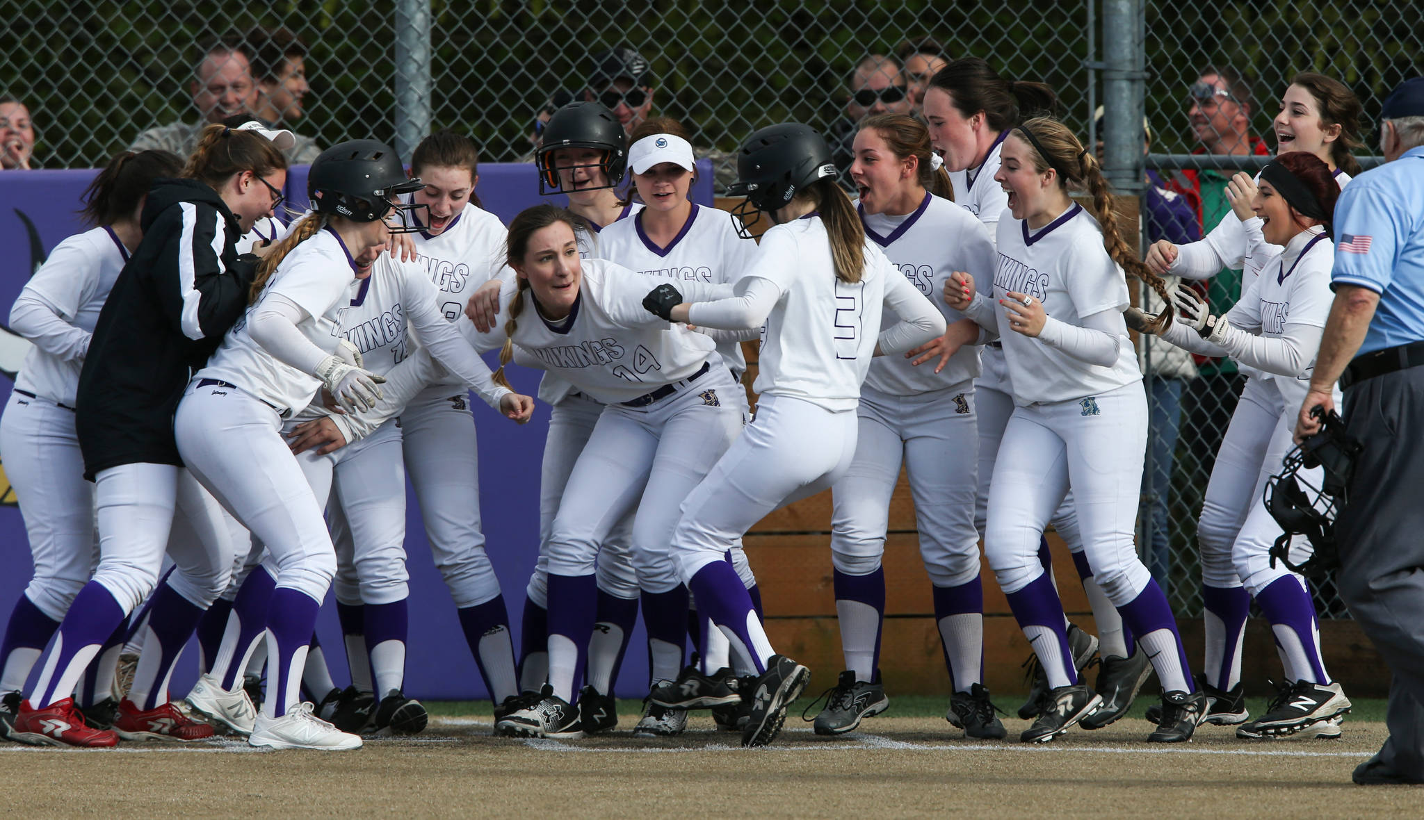 Lake Steven's Sara Johnson (14) holds back celebrating teammates so Emma Fortney (3) can touch home plate after hitting a 2-run homer to beat undefeated Jackson 3-1 on Tuesday, May 1, in Lake Stevens. (Andy Bronson / The Herald)