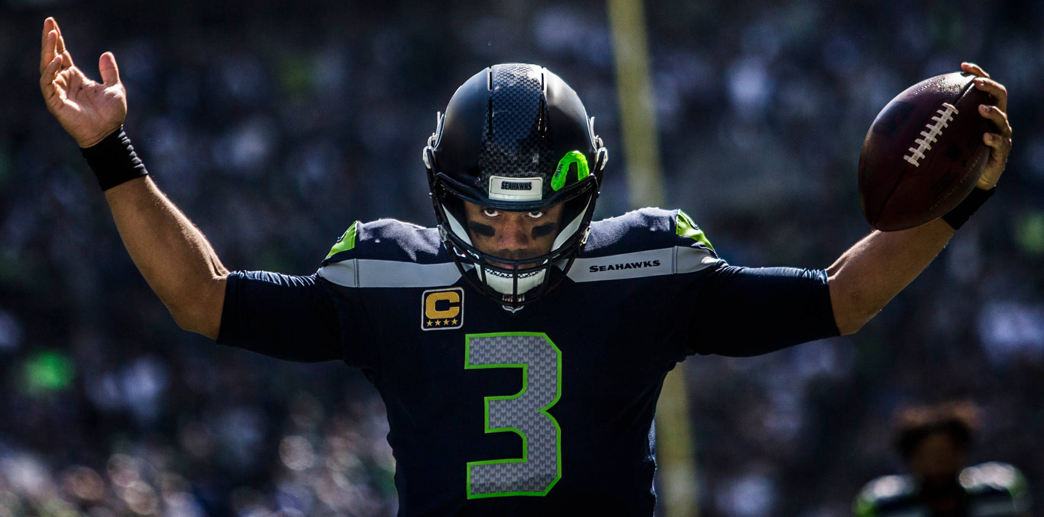 Seahawks' Russel Wilson raises his arms to pump the crowd up before the game against the Dallas Cowboys on Sept. 23, in Seattle. (Olivia Vanni / The Herald)