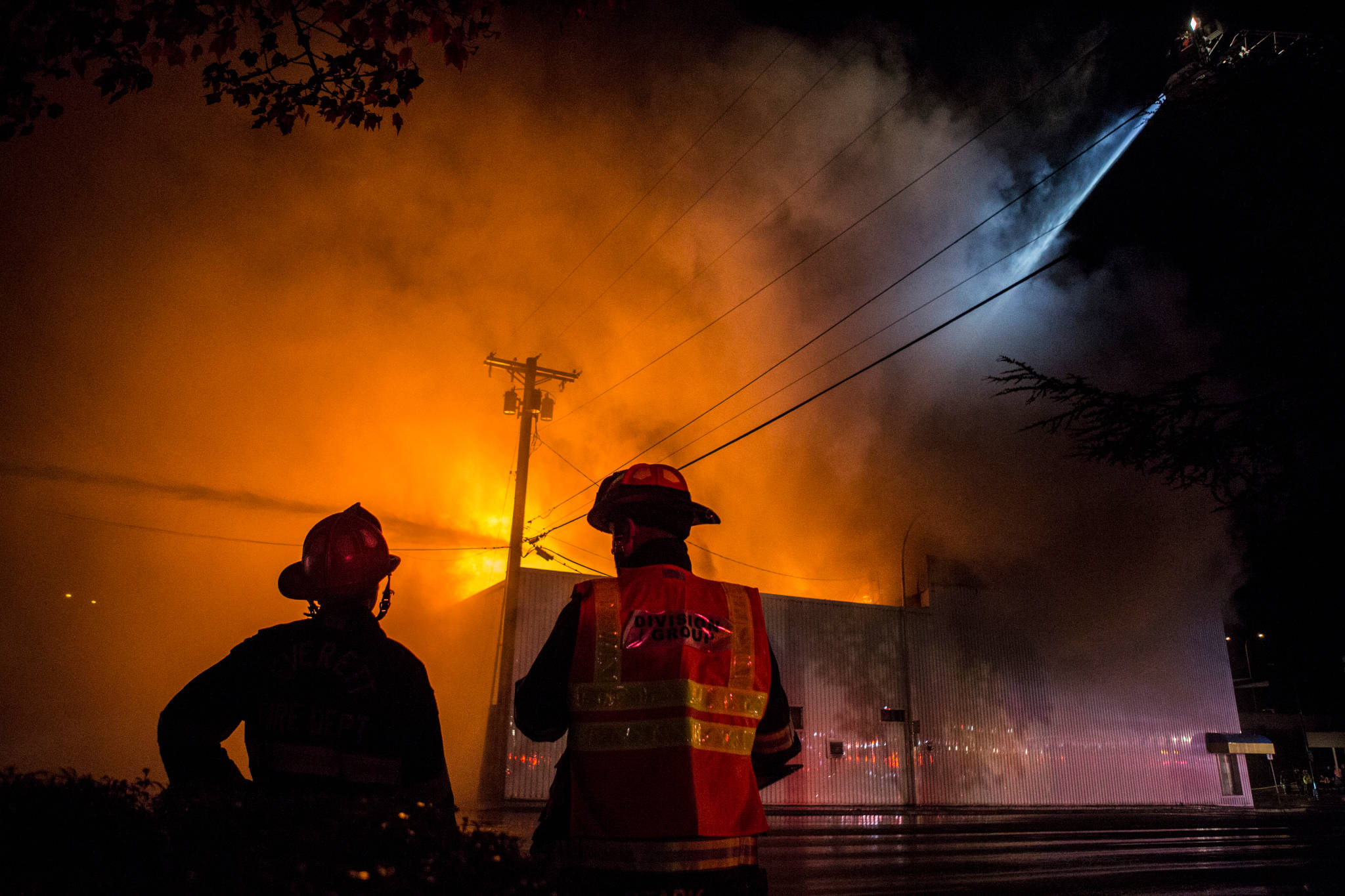Everett Fire Department firefighters watch as water is sprayed on the Judd & Black appliance store at 3001 Hewitt Ave on Sept. 21, in Everett. (Olivia Vanni / The Herald)