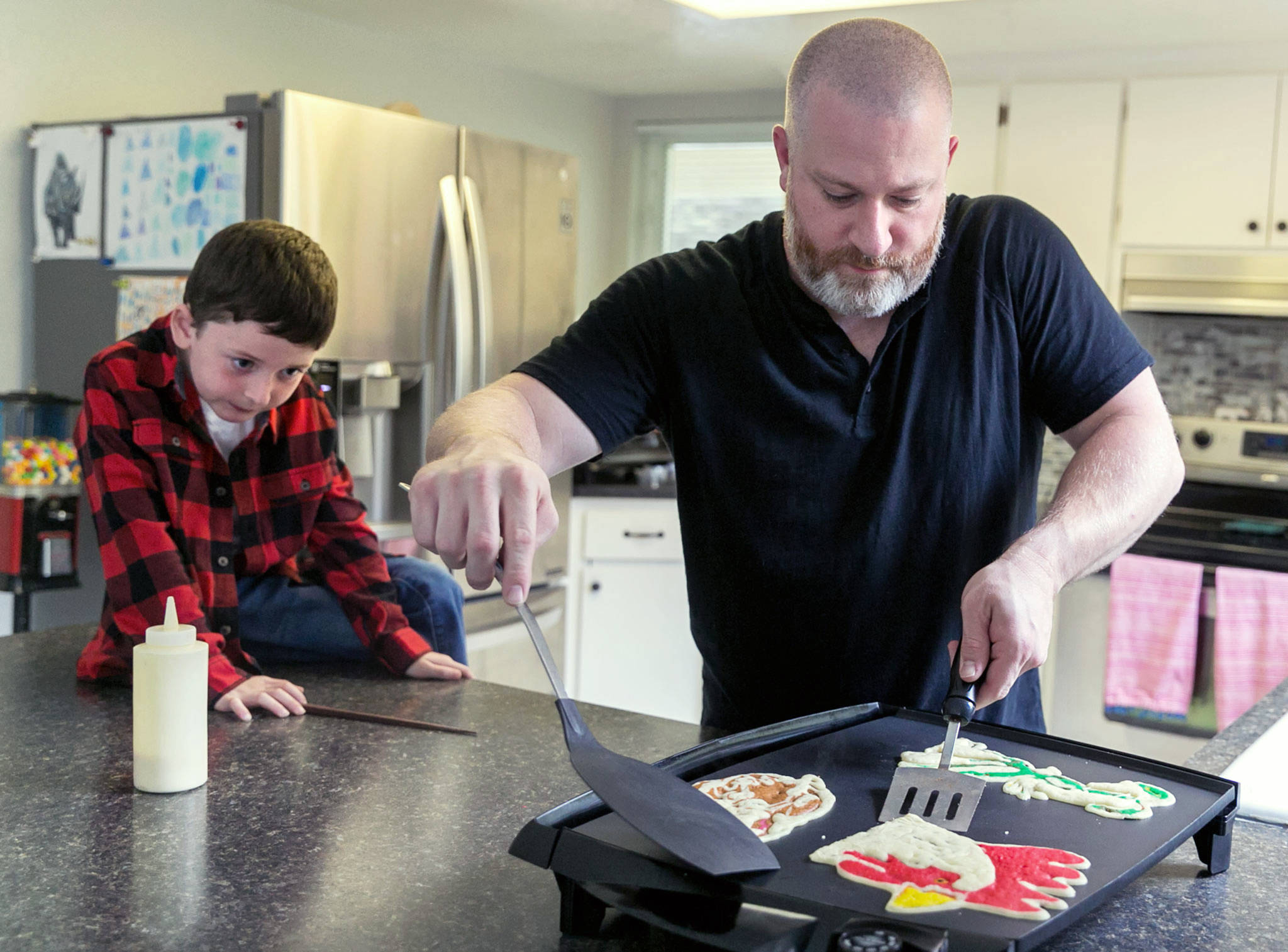 Pancake artist Brek Nebel demonstrates his artistry with his son Koen at their home in Snohomish on Sept. 29. (Kevin Clark / The Herald)