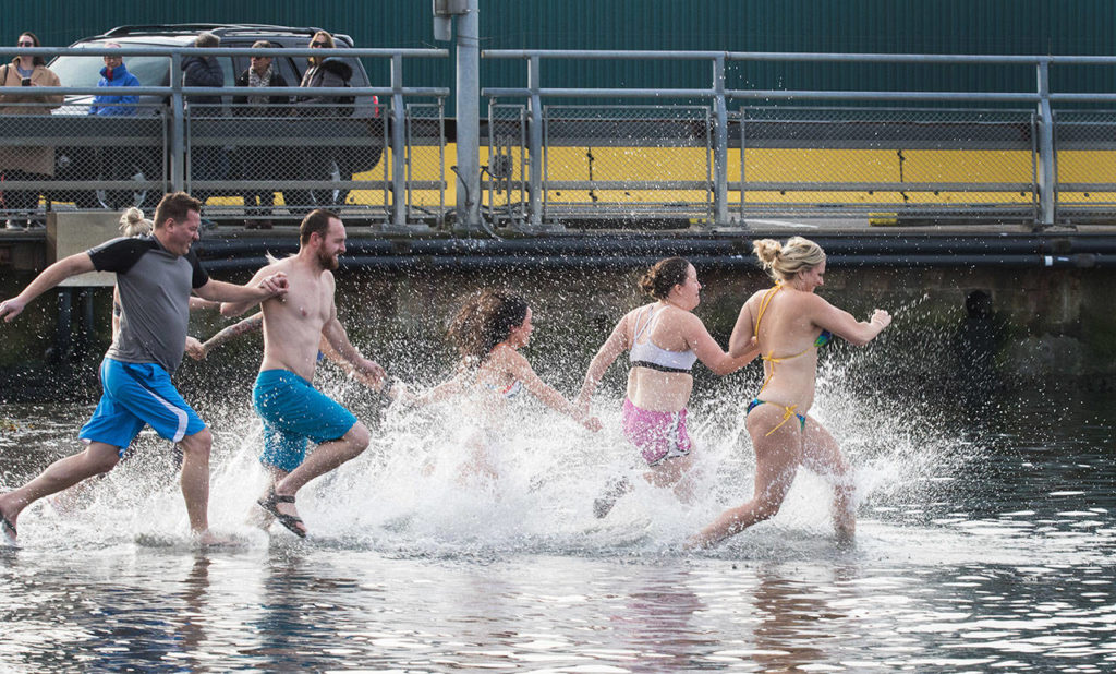 Late arrivals hit the water after the first wave of participants leave Tuesday, Jan. 1, during the annual Polar Bear Plunge at Brackett's Landing in Edmonds. (Andy Bronson / The Herald)