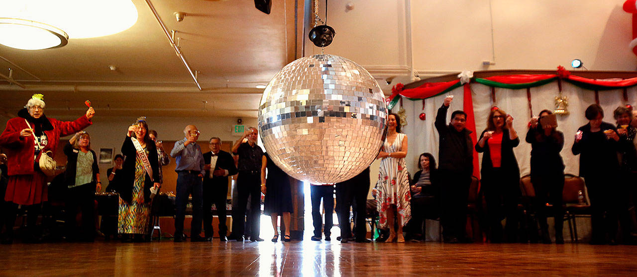 The partygoers line up to watch the glass ball lower to the floor during Monday afternoon's countdown to New Years…in Russia. (Dan Bates / The Herald)