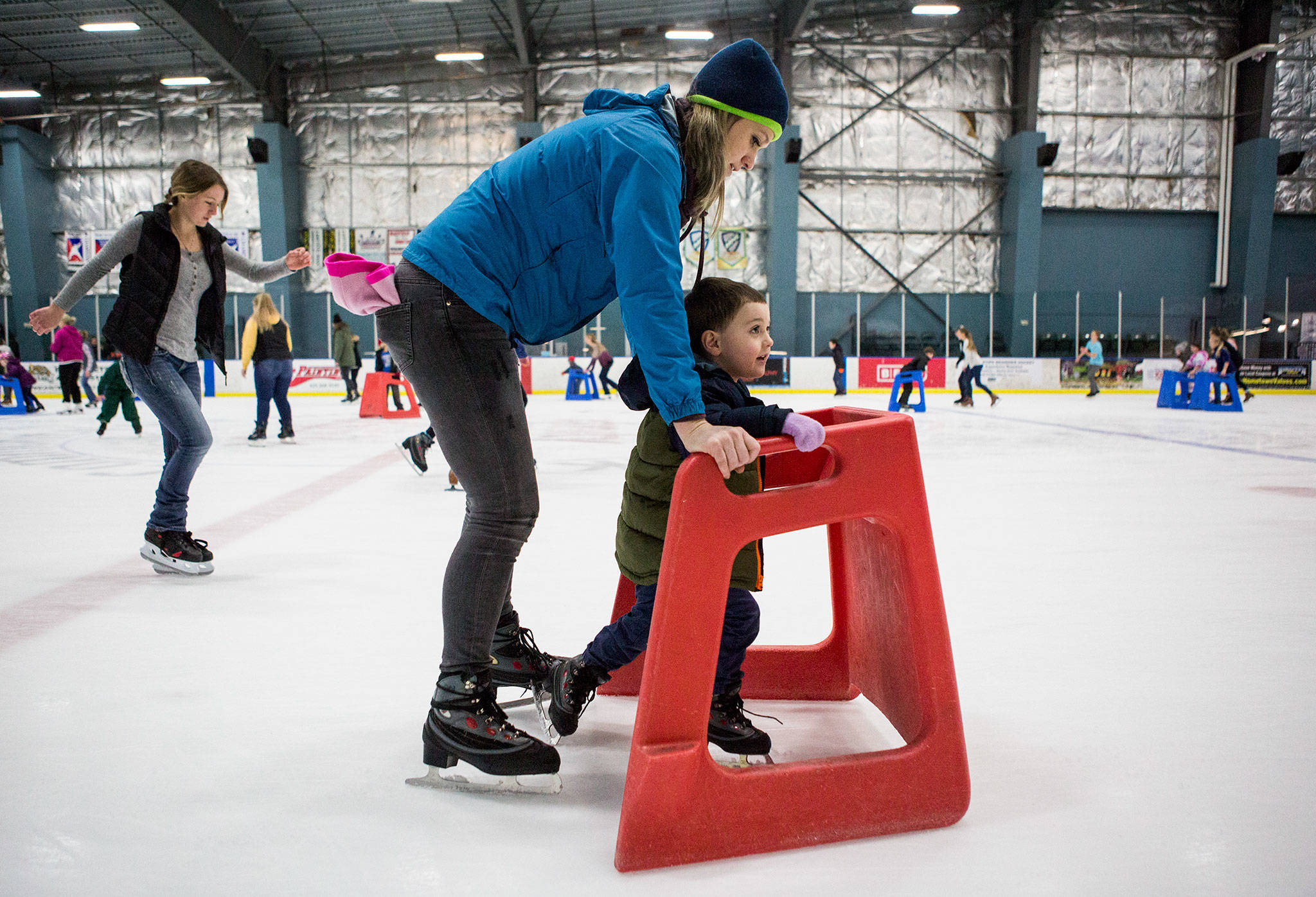Kellie Alleman helps her son Camden Alleman, 3, as he learns to skate with a walker at the Xfinity Community Ice Rink on Dec. 28 in Everett. (Olivia Vanni / The Herald)