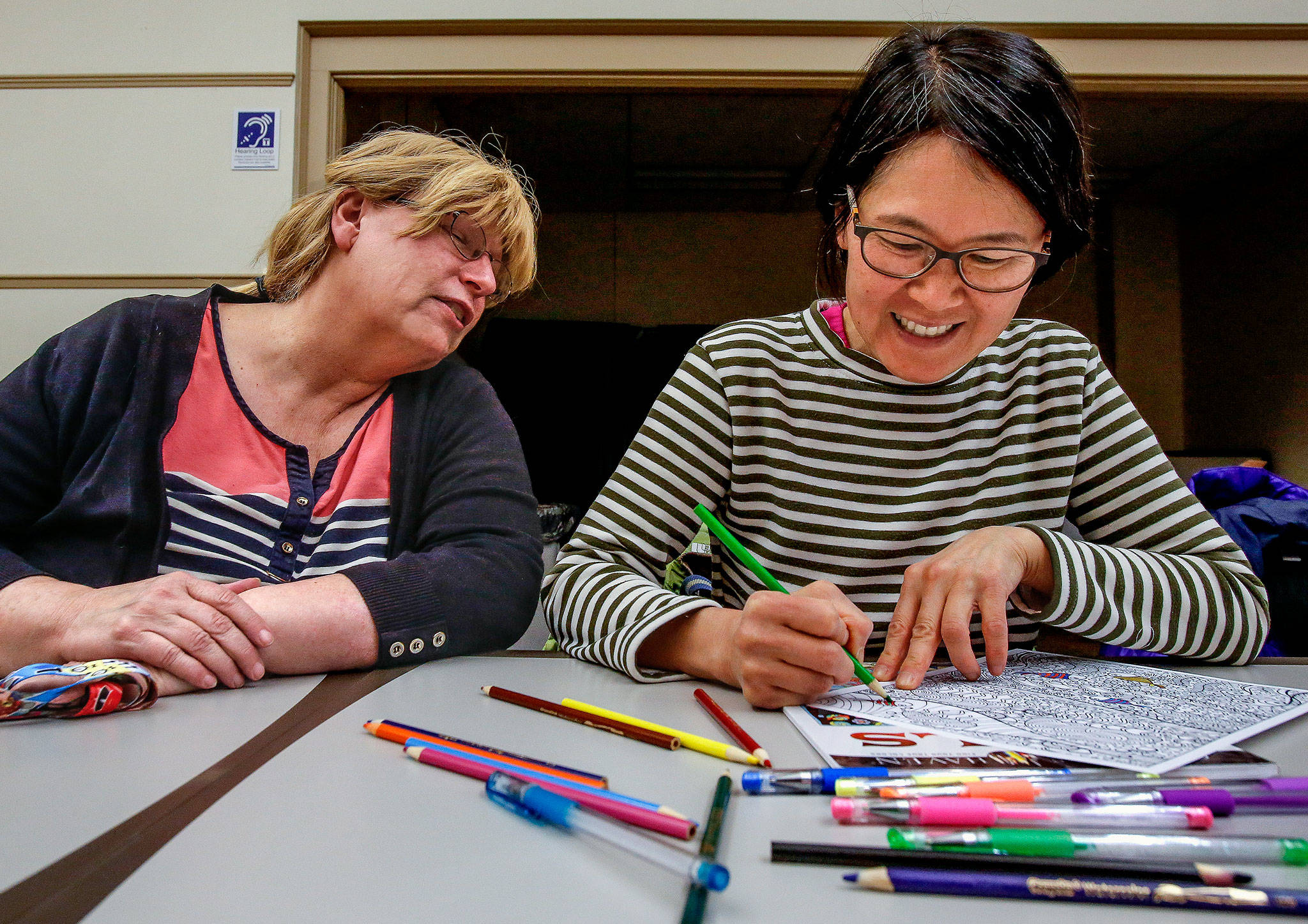 Library page Joanna Thomas (left) visits with Wai Ng, 59, while Ng gets started on a coloring project Wednesday night at the Everett Public Library's Coloring and Conversation. The program, which has become quite popular, was started by Thomas. It is free and takes place the first Wednesday of each month. (Dan Bates / The Herald)