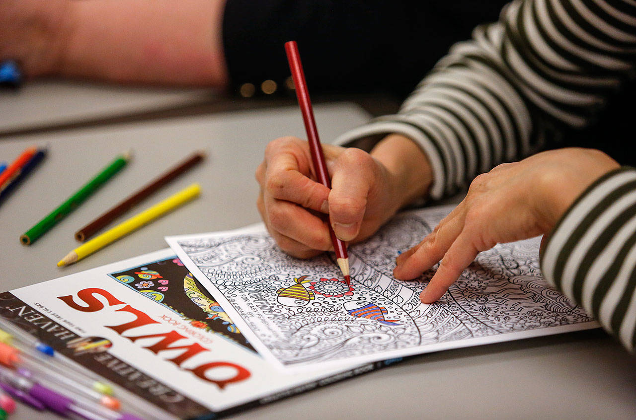 Wai Ng, 59, colors a highly detailed drawing at the Everett Public Library's Coloring and Conversation Wednesday evening. (Dan Bates / The Herald)