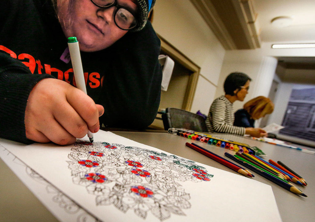 Jaiden Boss, 14, colors a printed drawing with ornaments from a Christmas book Wednesday at the library's Coloring and Conversation. (Dan Bates / The Herald)