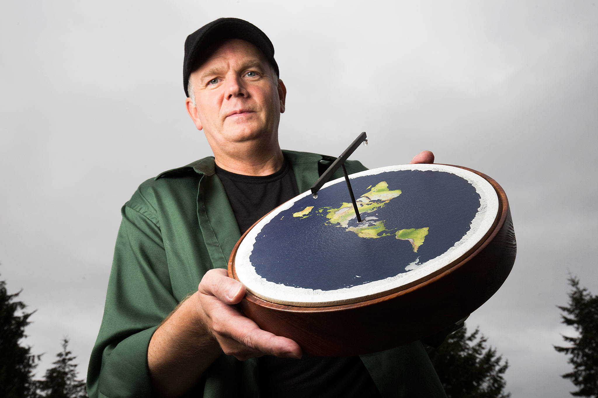 Mark Sargent holds a representative model of a flat planet. The Whidbey Island native has made a name for himself as a flat Earth spokesman. (Andy Bronson / The Herald)