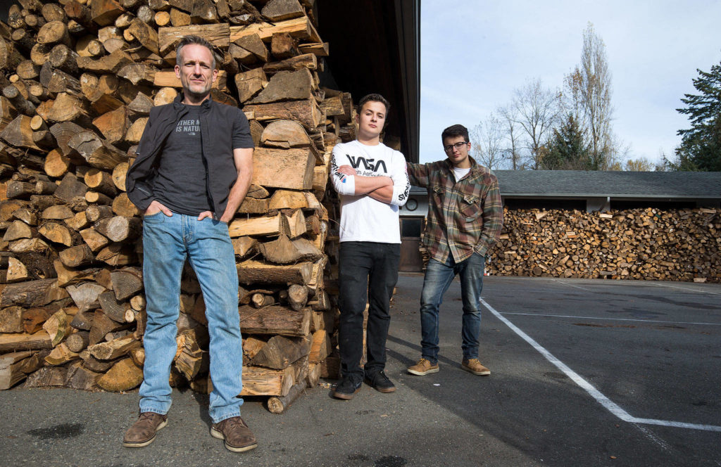 From left, Shane McDaniel and his twin sons, Harrison and Henry, 21, stand by wood stacked in front of their house in November. (Andy Bronson / The Herald)
