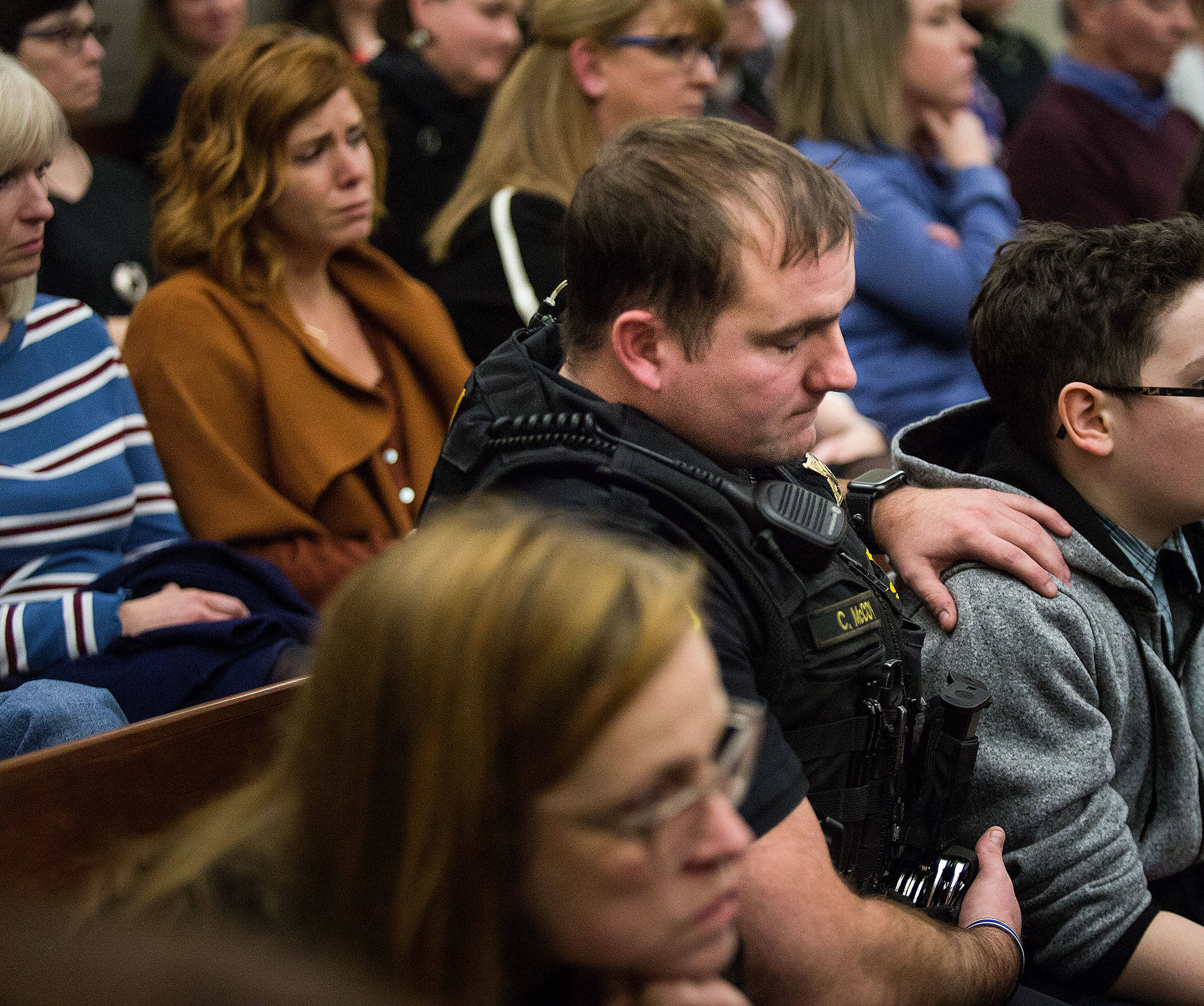 Snohomish County sheriff's deputy Cody McCoy places a hand on the shoulder of the son of Holly Martinez as Paul Martinez is sentenced Monday to 26 years behind bars for the murder of his wife. The sentencing took place at the Snohomish County Courthouse in Everett. (Andy Bronson / The Herald)