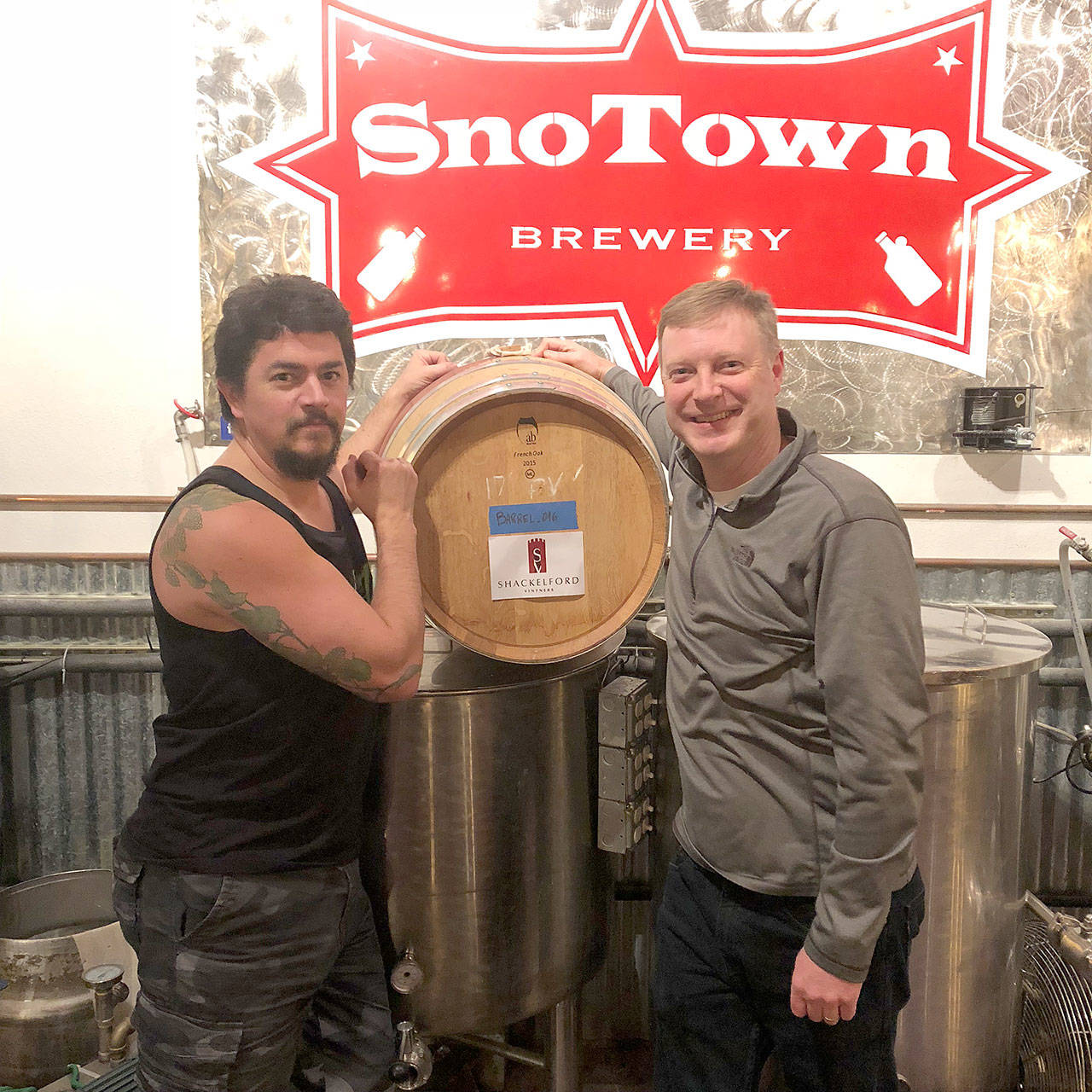 SnoTown Brewing's Frank Sandoval (left) and Shackelford Vintners' Ron Shackelford pose next to the red wine barrel Shackelford gave to Sandoval for aging one of his beers. (Photo by Aaron Swaney)