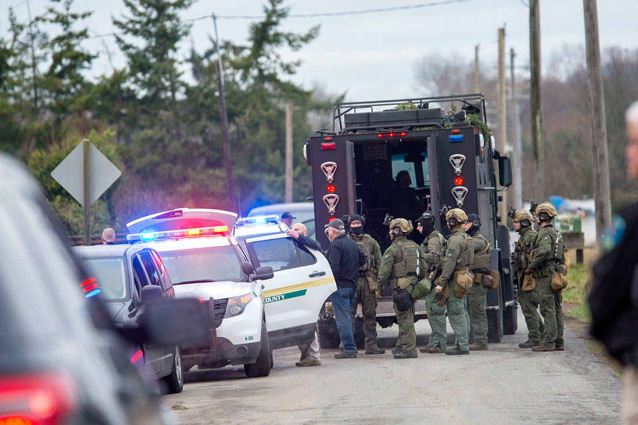 The State Patrol SWAT team gathers after serving a warrant Thursday morning that led to the arrest of a man suspected to be involved in the triple homicide discovered New Year's Eve. (Jesse Major / Peninsula Daily News)