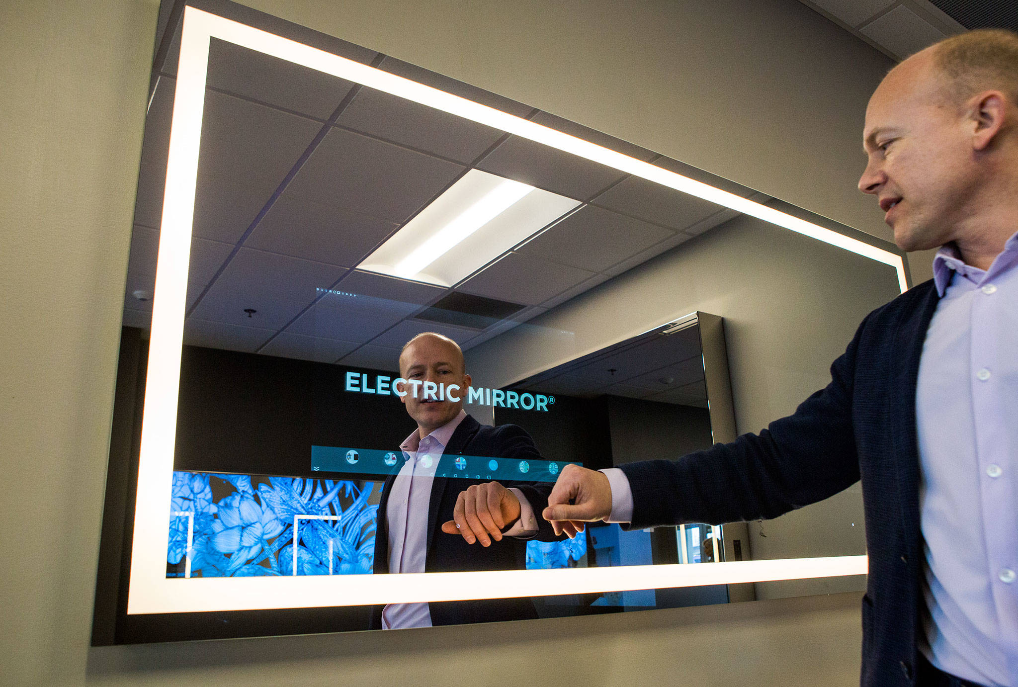 Electric Mirror President and CEO Jim Mischel demonstrates some of the features of the Everett company's new Savvy Home SmartMirror. (Olivia Vanni / The Herald)