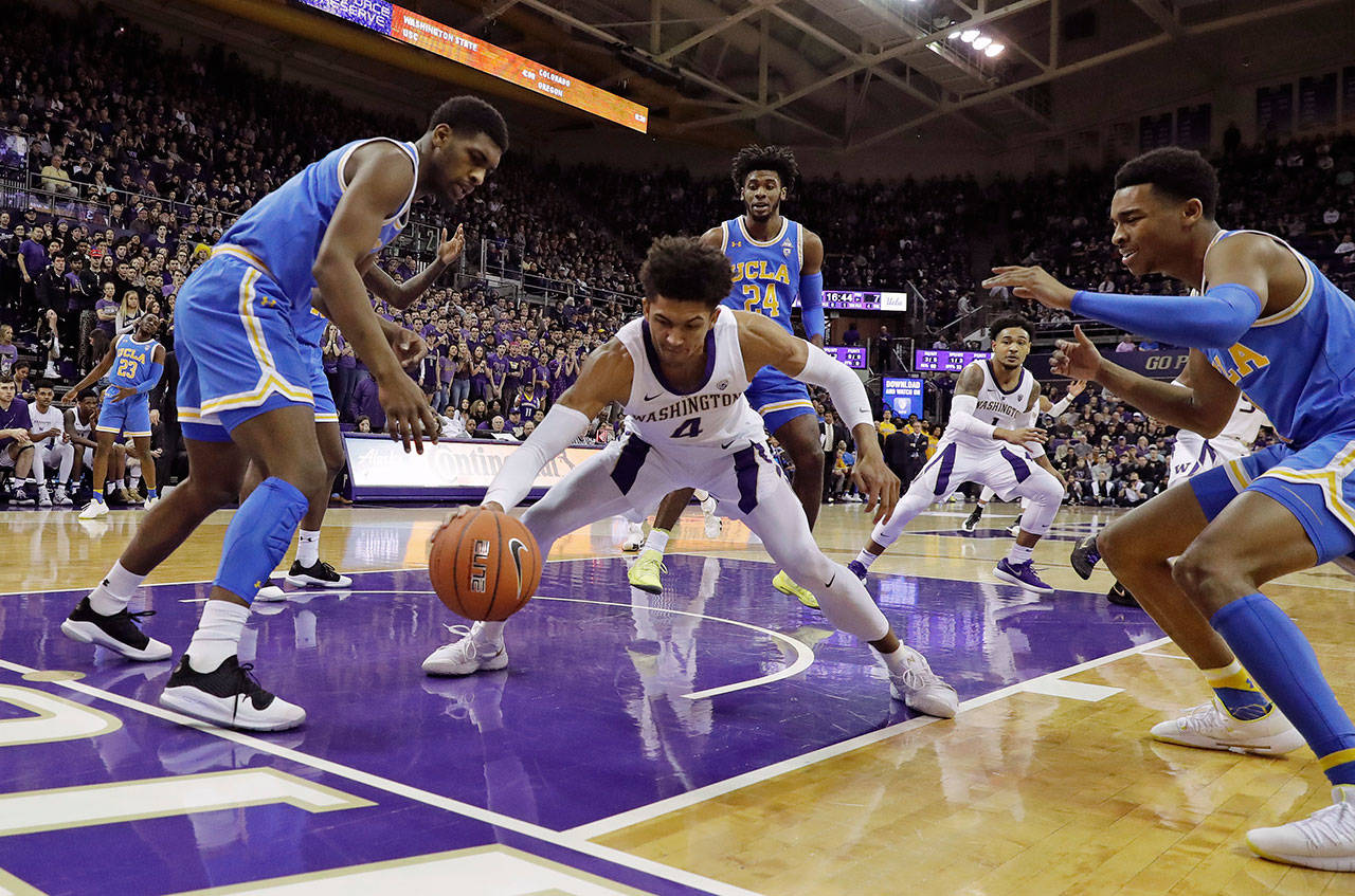 Washington guard Matisse Thybulle (center) drives between UCLA forward Cody Riley (left) and guard Jaylen Hands after making a steal during a game on Feb. 2, 2019, in Seattle. (AP Photo/Ted S. Warren)