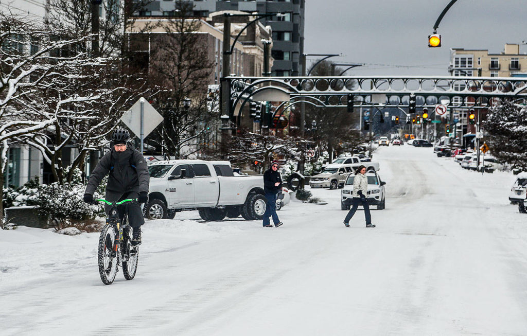 Colby Avenue in downtown Everett springs to life early Monday following a blanketing of snow overnight. (Dan Bates / The Herald)