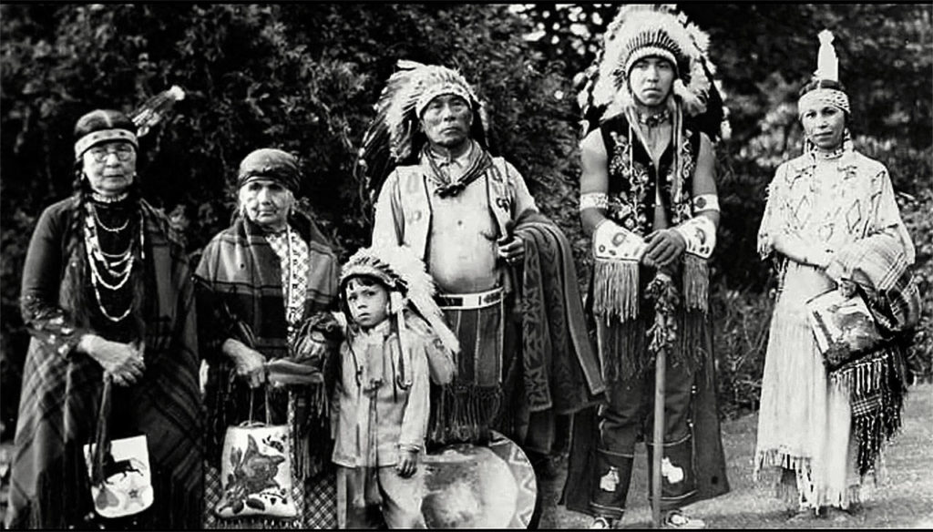 In ceremonial dress at Seattle's Volunteer Park in 1938, the Shelton family of Tulalip was photographed by Norman Edson. From left are Annie Frederick, Ruth Sehome Shelton, Wayne Williams, Chief William Shelton, Silas George and Harriette Shelton Dover. (Tulalip Tribes Hibulb Cultural Center)