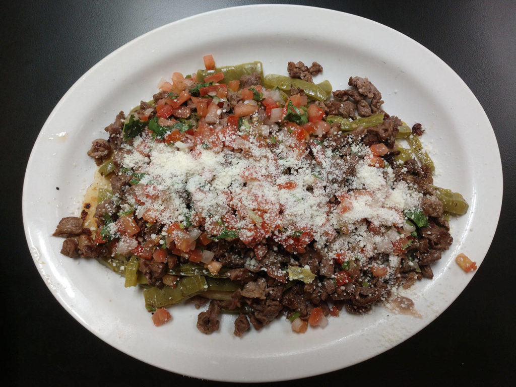 One of Tía Lety's bestsellers is the huarache. It's made with a corn dough base, fried in an oblong shape and topped with smashed pinto beans, queso fresco and a variety of other toppings. The dish gets its Spanish name from its sandal-like shape. (Sara Bruestle / The Herald)
