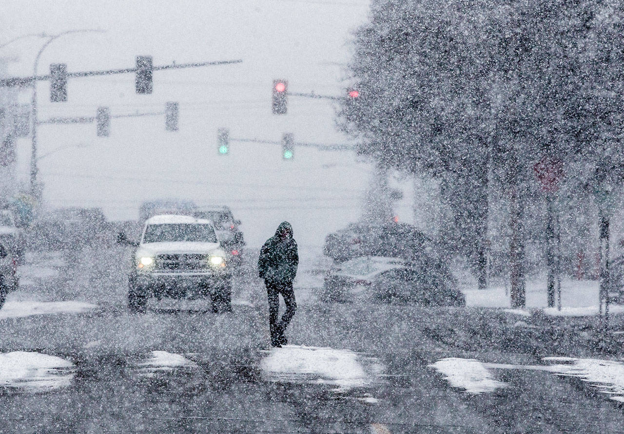 A pedestrian crosses California Street as snow begins to fall during the early afternoon on Friday in Everett. (Olivia Vanni / The Herald)