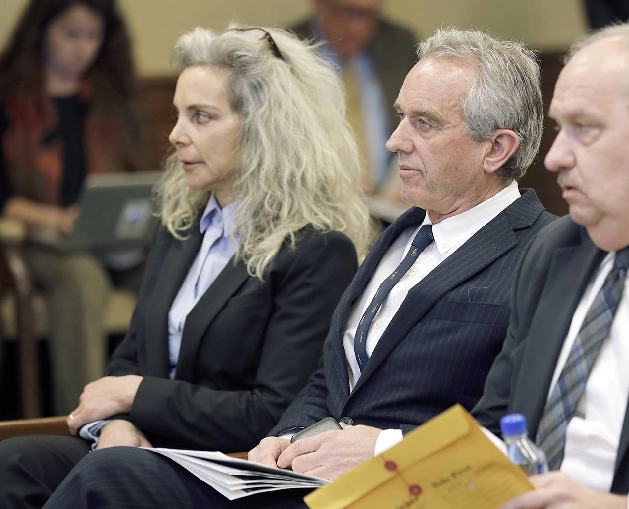 Robert Kennedy Jr. (center) and Dr. Toni Bark (left) wait to testify Friday during a public hearing before the House Health Care & Wellness Committee at the Capitol in Olympia. (AP Photo/Ted S. Warren)
