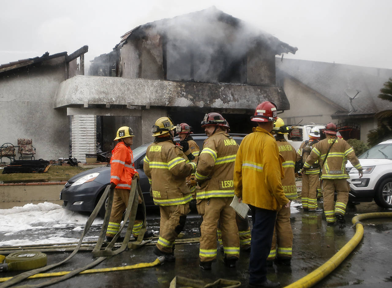In this Feb. 3 photo, firefighters suppress a fire at the scene of a deadly plane crash in the residential neighborhood of Yorba Linda, California. (AP Photo/Alex Gallardo, File)