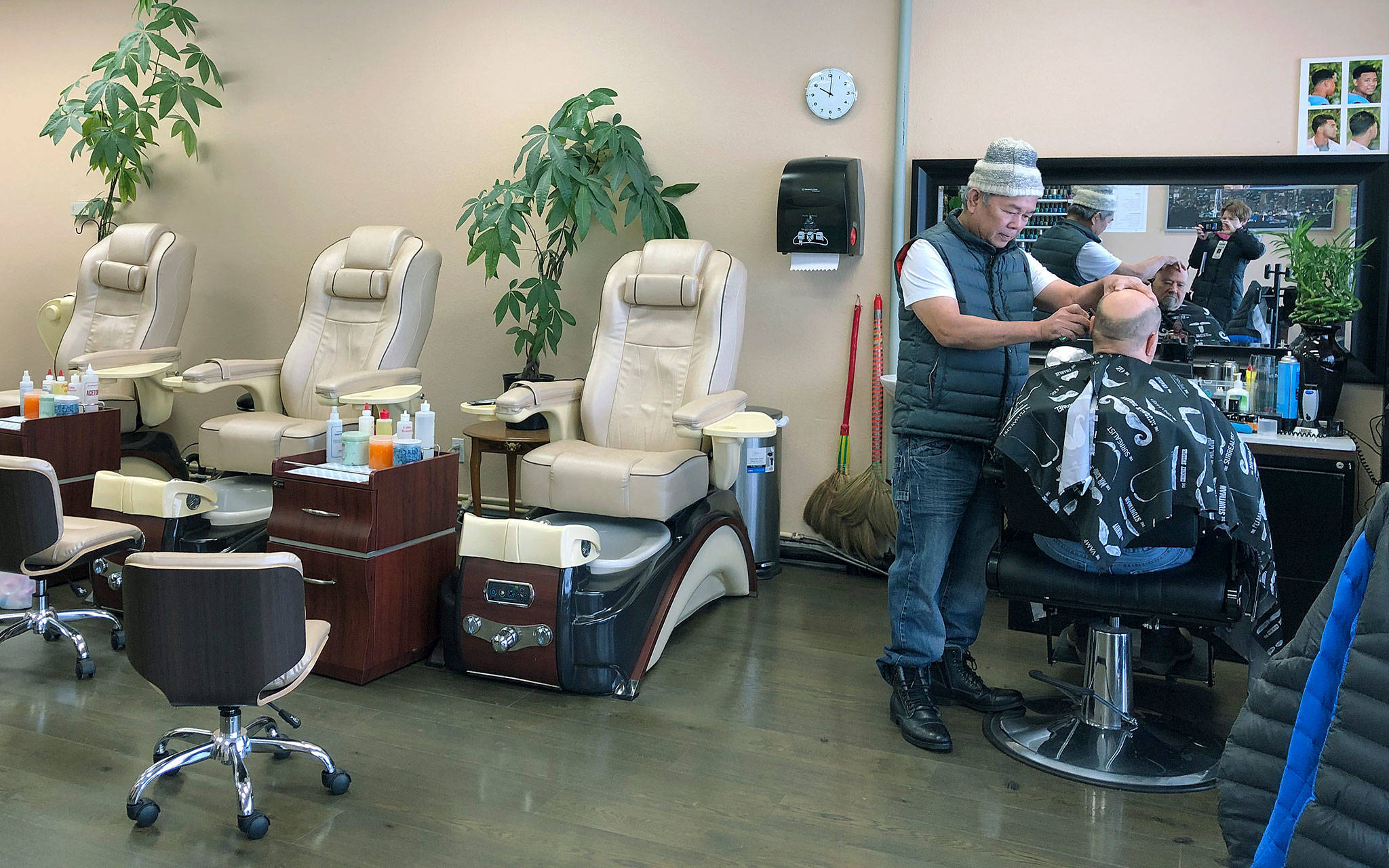 Tommy Nguyen, owner of Tommy Barber Nail Spa in Everett, cuts a customer's hair Monday. Nguyen closed the nail salon four days ago for a lack of business. (Janice Podsada / The Herald)