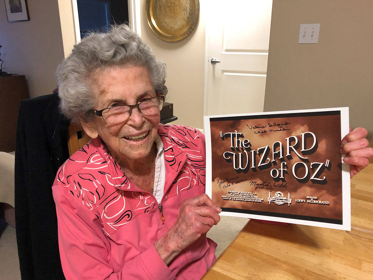 "Mercer Island resident Meredythe Glass poses with memorabilia from ""The Wizard of Oz."" Glass was an extra in the film, and will be the guest of honor at a party at her retirement community celebrating Hollywood on Feb. 22. Photo courtesy of Greg Asimakoupoulos"