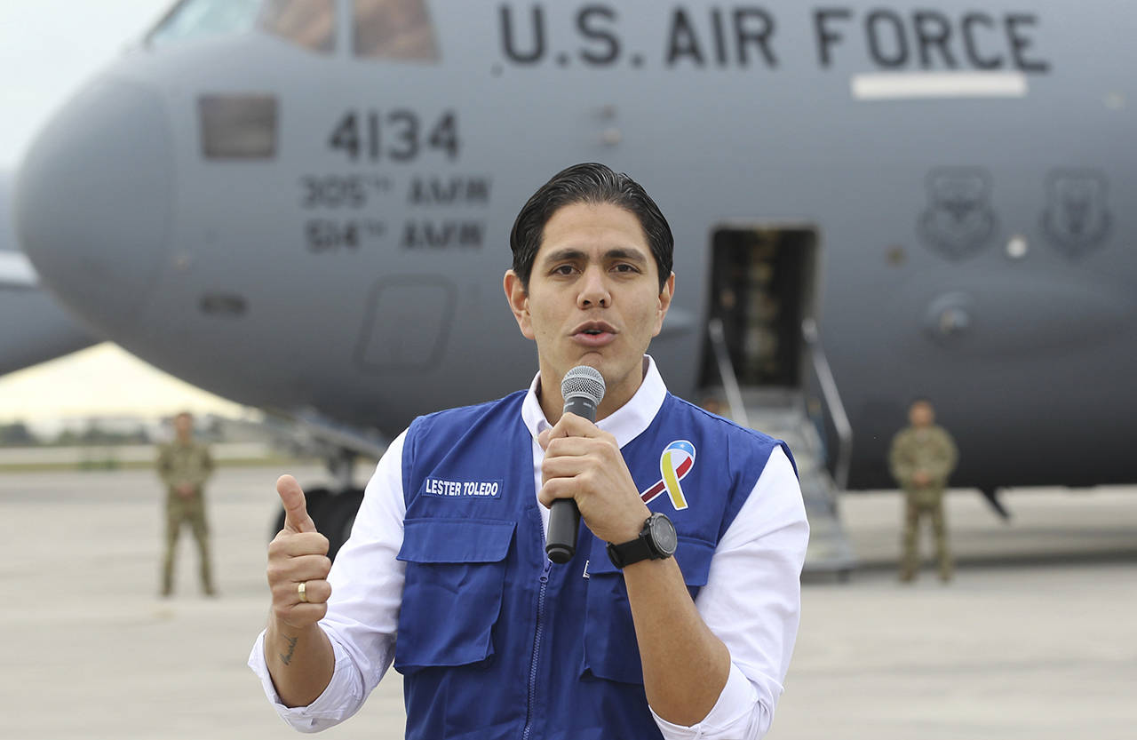 Lester Toledo from the Coalition Aid and Freedom Venezuela speaks in front of a C-17 cargo plane loaded with humanitarian commodities at Homestead Air Reserve Base on Saturday in Homestead, Florida. (AP Photo/Luis M. Alvarez)