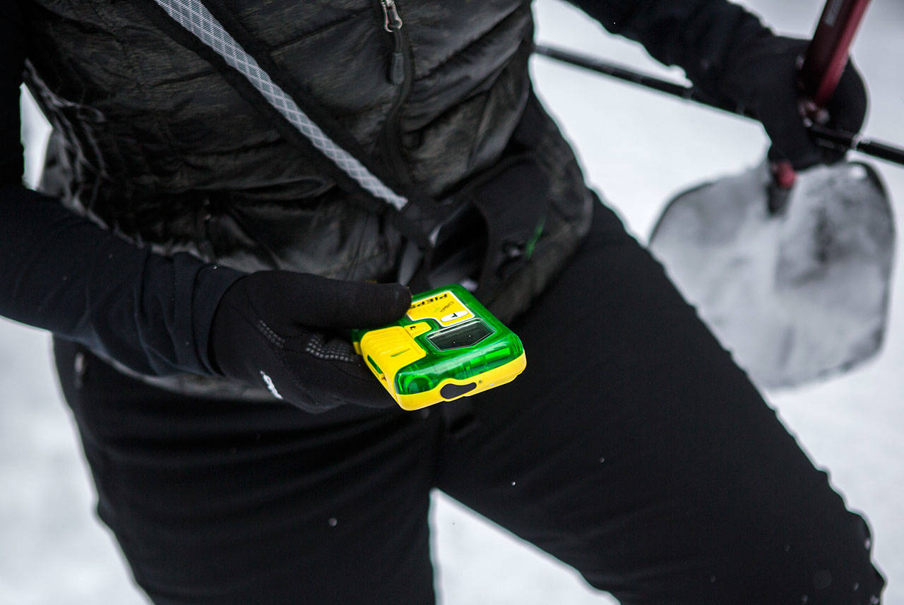 """Rhonda Miller demonstrates how to use an avalanche beacon during the """"Snowshoe with a Ranger"""" program on the Pacific Crest Trail North on Saturday near Stevens Pass. (Olivia Vanni / The Herald)"""