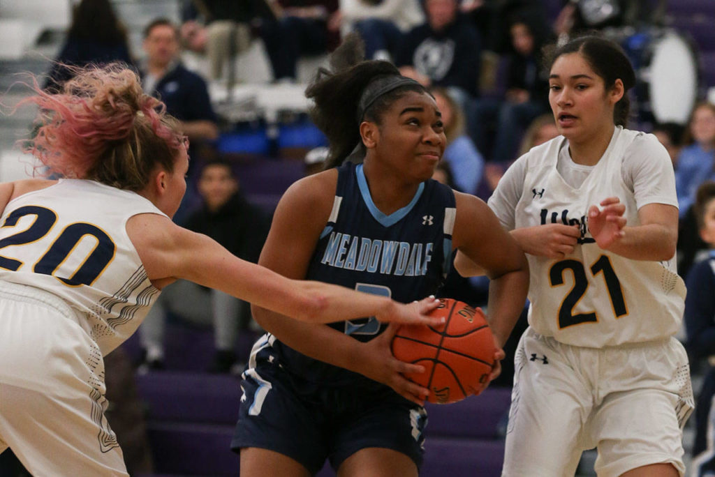 Meadowdale's Alicia Morrison drives the lane between two West Seattle defenders. Morrison helped the Mavericks mount a massive second-half comeback. (Kevin Clark / The Herald)