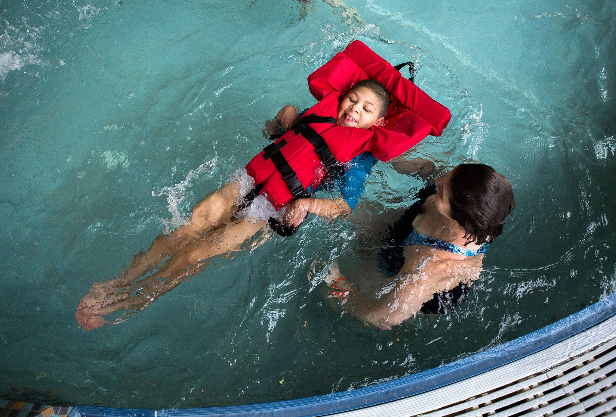 """<a href=""""https://www.heraldnet.com/news/doctors-said-he-might-not-live-past-5-he-just-turned-11/"""" target=""""_blank"""">Jamarious Carpenter</a>, 11, is guided through the water by his mother, Ginger Carpenter, during his birthday celebration at the Lynnwood Recreation Center & Pool on Jan. 20 in Lynnwood. (Olivia Vanni / The Herald)"""
