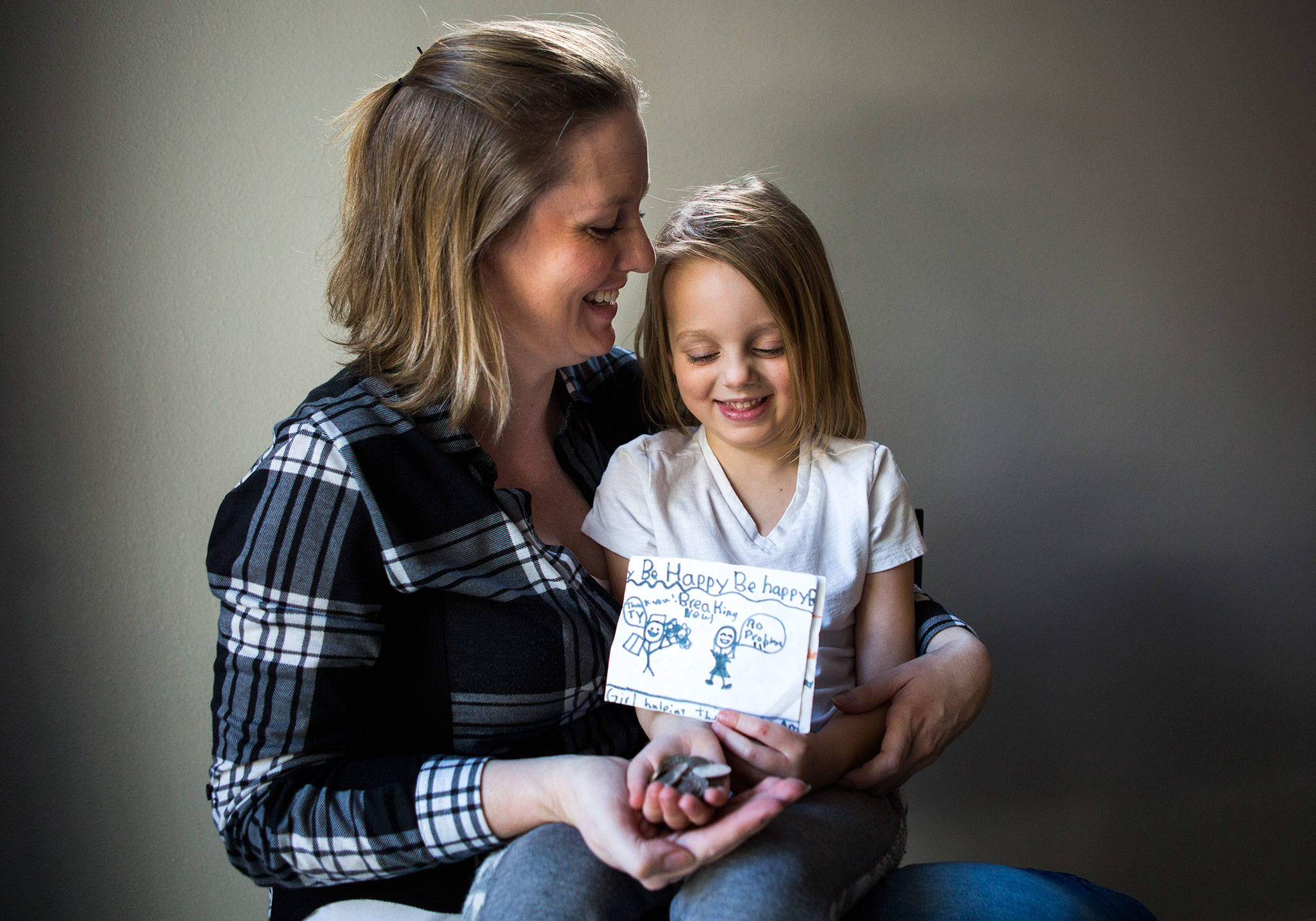 Jessica Beckstrand, left, sits with her daughter Layla, 4, holding some of the money raised and cards made for their family's non-profit, Strong Cares Guild, at their home on Tuesday, Feb. 26, 2019 in Marysville, Wash. (Olivia Vanni / The Herald)
