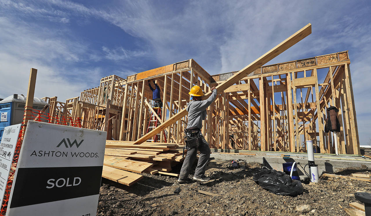In this Feb. 20 photo, a construction crew works on an already sold new home in north Dallas. (AP Photo/LM Otero)