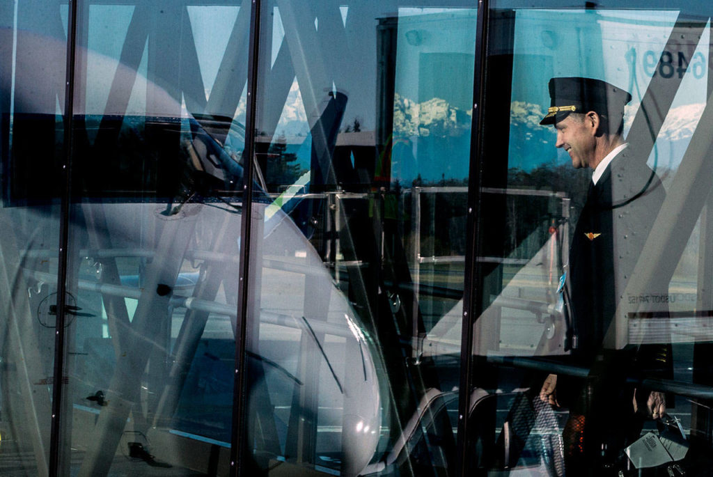 A pilot begins boarding the first plane scheduled during the grand opening of the Paine Field passenger terminal on Monday. (Olivia Vanni / The Herald)