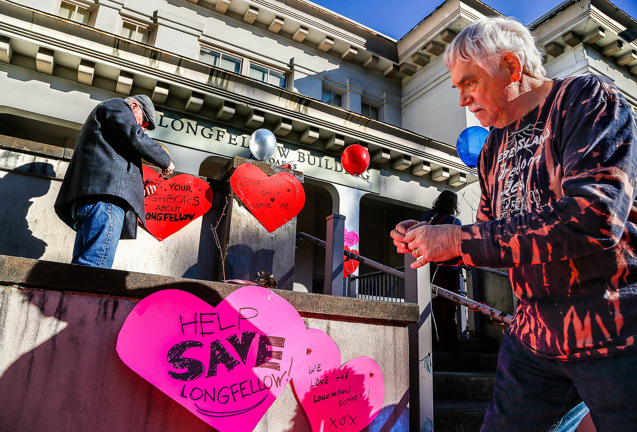 "photos by Dan Bates / The Herald                                 Local preservationists Paul Popelka (right) and Patrick Hall attach paper hearts with messages about the former Longfellow Scholl in Everett o Friday. They are ""heart-bombing"" the 108-year-old building to raise awareness of plans to demolish it for parking."