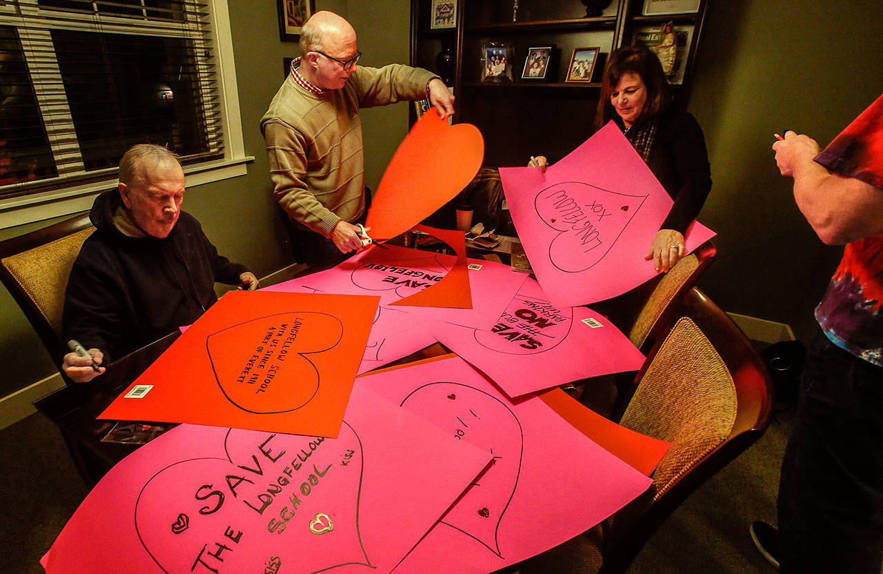 "Local preservationists Jack O'Donnell, (left) Patrick Hall, Andrea Tucker and Paul Popelka cut out, decorate and write messages on colorful paper hearts Thursday evening in advance of Friday's ""heart-bombing."" (Dan Bates / The Herald)"
