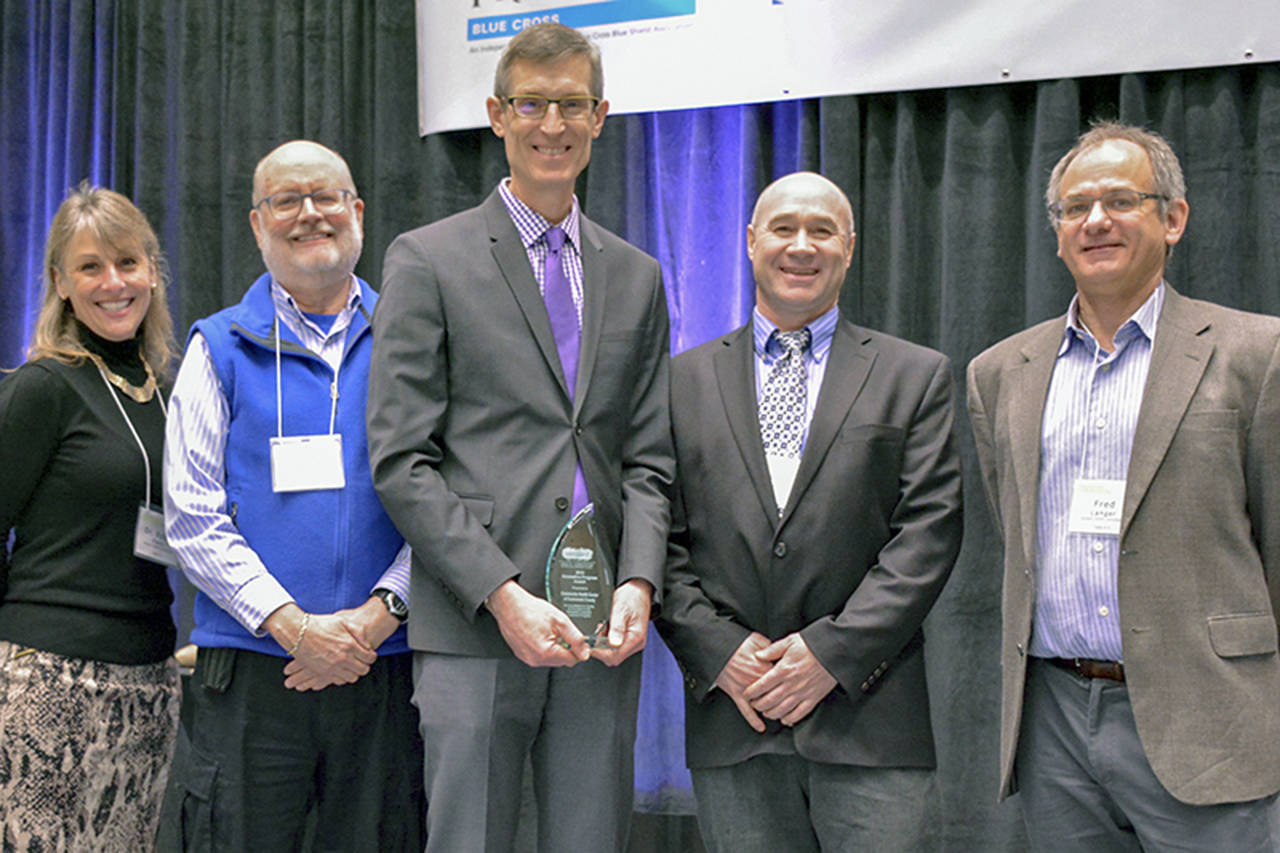 Dr. Tom Tocher (center) of Community Health Center of Snohomish County accepts the Innovative Program Award from (left to right) Verdant Superintendent Dr. Robin Fenn, Commissioner Dr. Jim Distelhorst, Commissioner Bob Knowles, and Commissioner Fred Langer at the Verdant Healthier Community Conference. (Submitted photo)